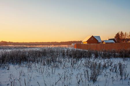 Winter sunset in field near the village photo
