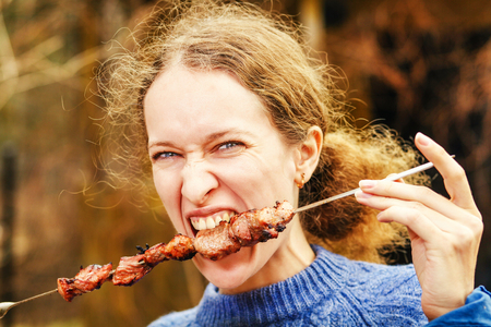 Woman eating shish kebab on picnic photo