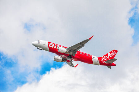 scheduled: PHUKET, THAILAND- OCTOBER 21, 2014: AirAsia plane takes off from Phuket Airport. AirAsia group operates scheduled domestic and international flights to 100 destinations spanning 22 countries