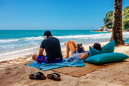 PHUKET, THAILAND- OCTOBER11, 2014: man listening music, woman using tablet on Surin beach. Surin is exclusive beach retreat for discerning travelers and couples seeking relaxation in a serene setting