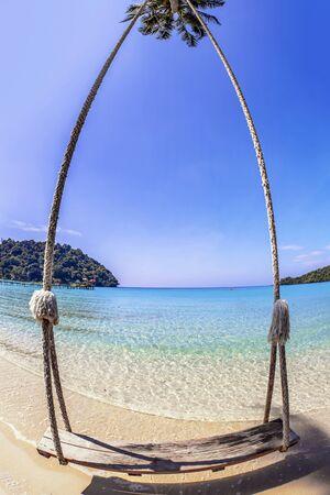 Swings and palm on the sand tropical beach. Fisheye look photo