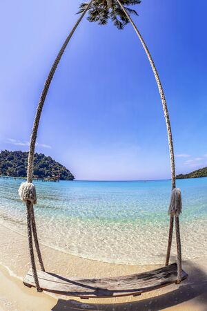 Swings and palm on the sand tropical beach. Fisheye look photo