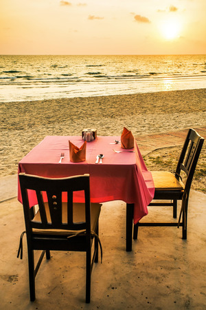 romantic beach: Dining table prepared for two on white sand beach close to sea