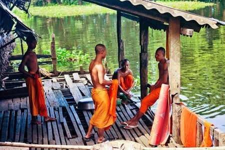 16 17: SIEM REAP, CAMBODIA - NOVEMBER 17, 2011: Buddhist monks talking near the Tonle Sap lake. Tonle Sap, the largest body of water Indochina during the rainy season, the area of 16,000 square km Editorial