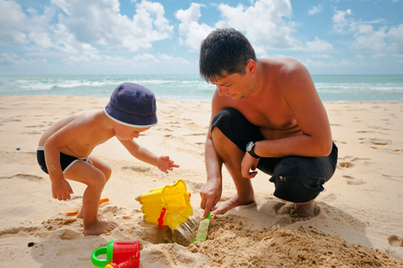 happy holidays: Boy and dad playing in the sand on the beach