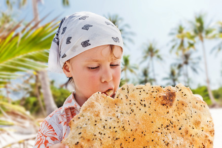 beautiful baby: Portrait of little boy eating a cookie at the beach Stock Photo