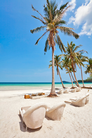 lounges: Beautiful tropical beach with  lounges and palms under blue sky at Phu Quoc island  in Vietnam. Stock Photo