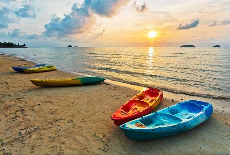 white sand beach: Kayaks on the beach during sunset
