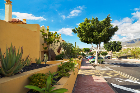 adeje: TENERIFE ISLAND, SPAIN - OCTOBER 28, 2015 : Street with typical Canary style holiday apartments in Costa Adeje, Tenerife, Canary Islands