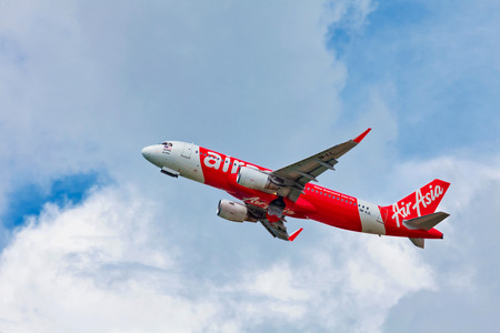 scheduled: PHUKET, THAILAND- OCTOBER 25, 2014: AirAsia plane takes off from Phuket Airport. AirAsia group operates scheduled domestic and international flights to 100 destinations spanning 22 countries