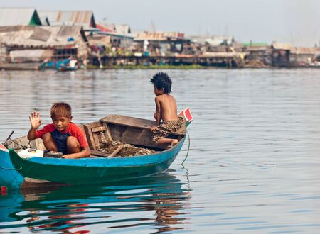 peaking: SIEM REAP, CAMBODIA-NOVEMBER 17, 2011: An unidentified boys on a boat floating on Tonle Sap lake in Siem Reap. Tonle Sap is the largest lake in SE Asia peaking at 16kkm2 Editorial