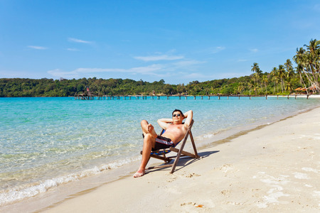 relaxing man at the empty tropical beach