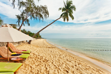 Beautiful tropical beach with  lounges and palms under blue sky at Phu Quoc island  in Vietnam. Stock Photo