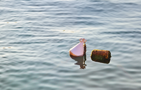 Single white buoy on a calm sea surface  Stock Photo