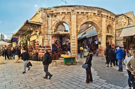JERUSALEM, ISRAEL - DECEMBER 26, 2016: medieval gate leads to the Aftimos Bazaar with its noisy merchants and colorful goods in the Christian quarter of the old city of Jerusalem
