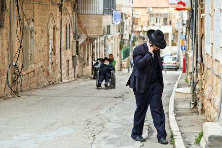 JERUSALEM, ISRAEL - DECEMBER 29, 2016: Orthodox Jewish man with mobile phone walk at street at jewish quarter in Jerusalem.