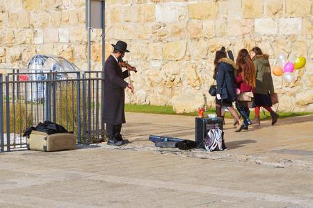 jaffa: JERUSALEM, ISRAEL - DECEMBER 26, 2016:  A Jewish man in orthodox clothes plays the violin near the Jaffa gate to the old town of Jerusalem. Editorial