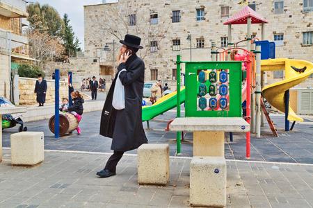 rabbi: JERUSALEM, ISRAEL - DECEMBER 29, 2016: Orthodox Jewish man with mobile phone walk at street at the playground in jewish quarter.