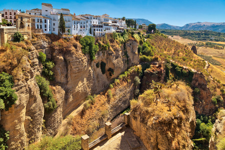 View of the buildings standing on the edge of a cliff in Ronda town, Spain Stock Photo