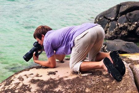 A young photographer takes a picture on a stony beach photo