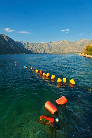 Row of red and yellow buoys in sea. Montenegro Stock Photo