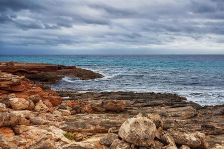 Rocky beach under a gloomy dramatic sky. Mallorca island, Spain Mediterranean Sea, Balearic Islands.