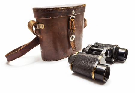 Old binoculars on a white background. Фото со стока