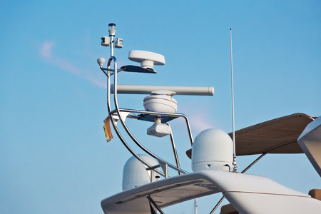 Closeup view of navigation radar system antennas yacht on blue sky background