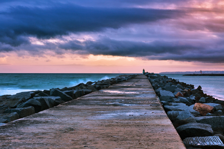 Pier to famous old farol de Portimao molhe este under gloomy sunset. Portugal