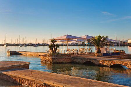 Jetée en pierre avec tables et parasols cafe tôt le matin à Port de Pollença, Majorque, îles Baléares, Espagne Banque d'images