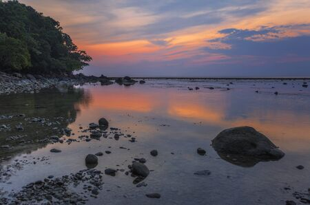 Tropical beach in ebb time on sunset background. Nai Yang beach. Phuket. Thailand