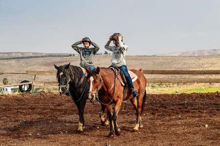 JERUSALEM, ISRAEL - DECEMBER 28, 2016: Children are taught to ride horses on a farm in the village of Tekoa near Jerusalem. Editorial