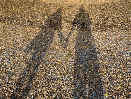 woman shadow: Shadow of woman and man holding hand, together Stock Photo