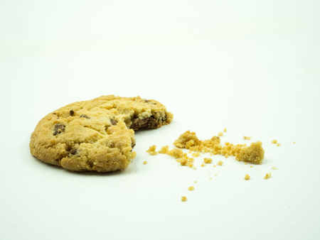 Chocolate chip cookie and crumbs on white background Фото со стока