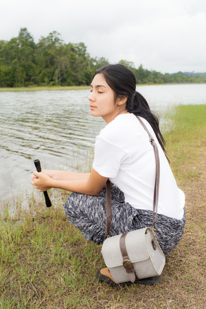 using binoculars: Young asian woman using binoculars in the topical forest.