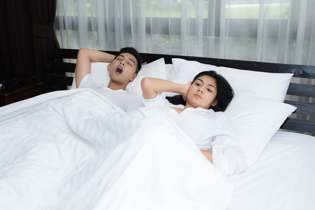Couple in bed, man snoring on the bed in the bedroom and woman can not sleep