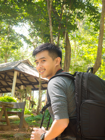 Handsome asian man with backpack taking a photo with mirrorless camera.