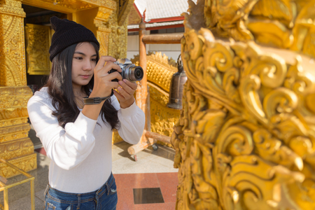 Asian woman taking photo with mirrorless camera at Wat Sri Phanton Buddhist Temple in Nan Province Northern Thailand 版權商用圖片