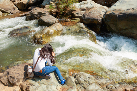 Beautiful asian woman taking a photo around mountains near the river at spring time with camera 版權商用圖片
