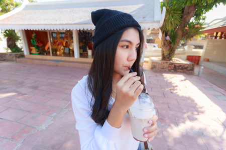 Asian woman drinking coffee with tube from plastic glass.