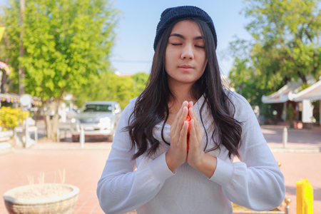 Asian woman pay homage to a Buddha image.