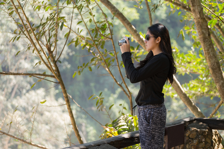 Beautiful asian woman with backpack taking a photo with mirrorless camera.