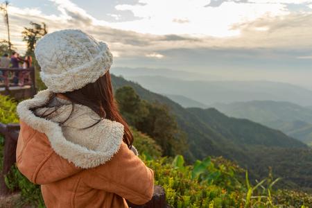 Beautiful asian woman relaxing on top of a mountain and enjoying sunrise 版權商用圖片