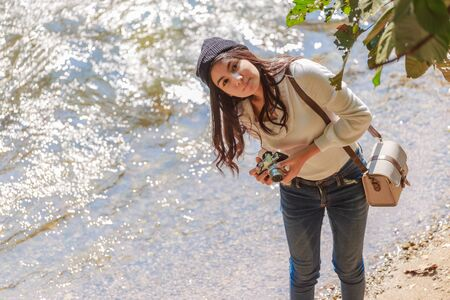 Beautiful asian woman hiking around mountains near the river at spring time with camera