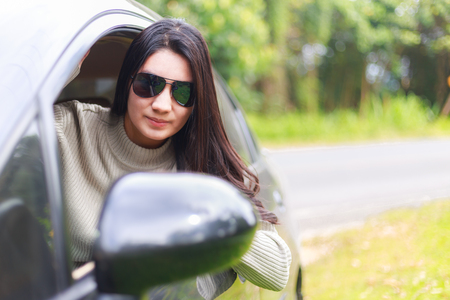 Beautiful asian woman wearing black glasses protrudes from the window of the car with smiling for the road trip