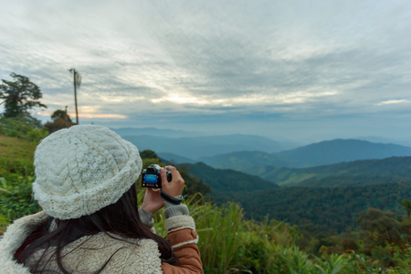 Asian woman photographer taking photo of landscape from top of the mountain in the morning with sunrise 版權商用圖片
