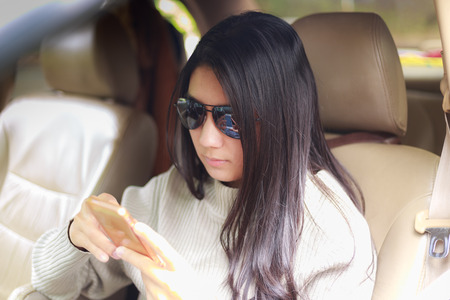Beautiful asian woman wearing black glasses playing smartphone in the car on the trip 版權商用圖片