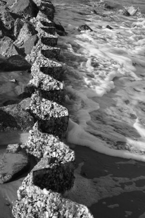 Sea Foam forming against a curvy wall photo