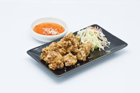 fried chicken in black plate with sauce on white background