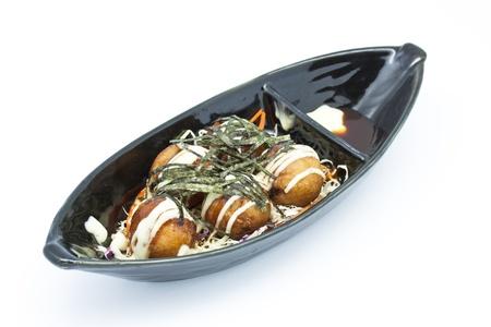 Japanese takoyaki balls in black plate with sauce Stock Photo